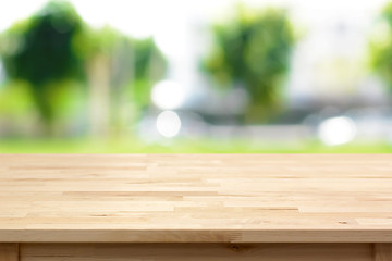 Wood table top on blurred green tree background