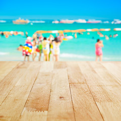 Wood table top on blur beach background with people in colorful clothes