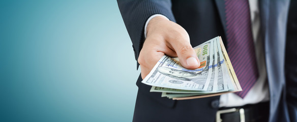 Businessman giving money,   united states dollar (USD) bills, on gray background