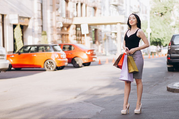 Fashionably dressed woman with colored shopping bags, shopping concept