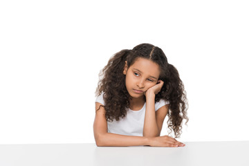 Portrait of bored little girl sitting at table and looking away isolated on white