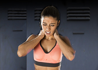 attractive hispanic fitness woman touching and grabbing her neck and upper back suffering cervical pain