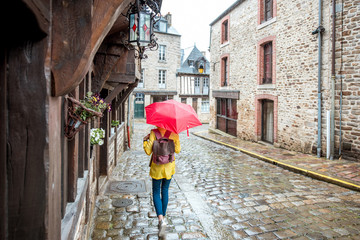 Young woman in yellow raincoat walking with umbrella in Dinan village at Brittany region in France