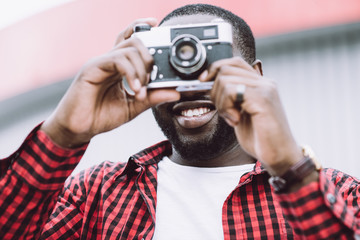 Outdoor summer smiling lifestyle portrait of handsome and happy Afro American tourist having fun in the city in Europe with camera travel photo of photographer making pictures in hipster style