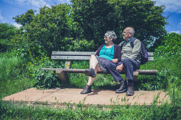 Senior couple relaxing on bench in nature