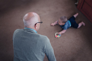Grandfather watching grandson play