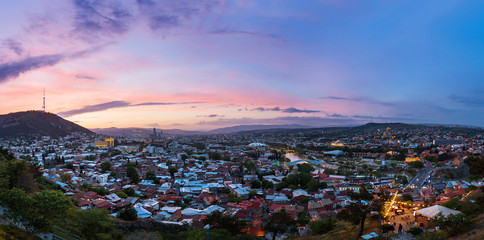 Sunset panorama view of Tbilisi, capital of Georgia country. Famous landmarks -  Metekhi church, Holy Trinity Cathedral (Sameba), Presidential Administration, Bridge of Peace
