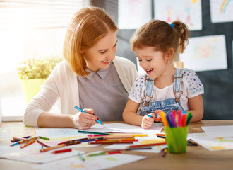 mother and child daughter draws in creativity in kindergarten