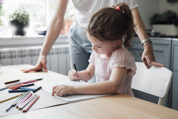 Cute little Caucasian girl drawing with crayons on kitchen table.
