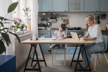 Beautiful Caucasian blonde woman typing on laptop and sitting at kitchen with her cute little daughter.