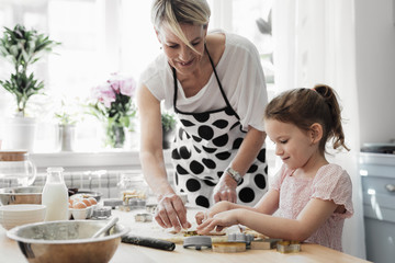 Cute little Caucasian girl enjoying making pastry with her mother at kitchen at home.