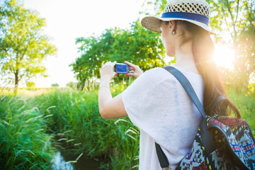 Beautiful caucasian model standing in the nature on a footbridge over small stream wearing casual summer clothes, straw hut and backpack, taking photo with a small digital camera. Summer sunset.