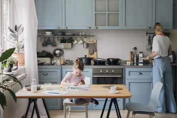 Mother and daughter spending time at kitchen at home.