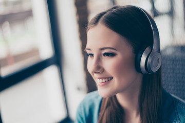 Close up portrait of attractive young girl in modern headphones. She is dreamy and excited, listening to her favourite song, smiling