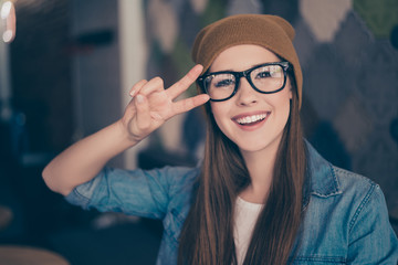 Close up portrait of cheerful playful girl, who is gesturing peace sign and smiles. She is wearing casual clothes, glasses and a brown hat