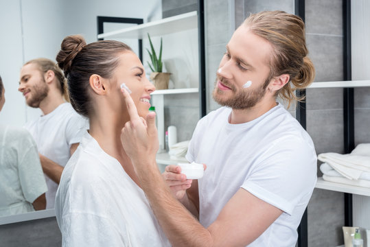 Young bearded husband applying face cream on cheek of his wife  in bathroom
