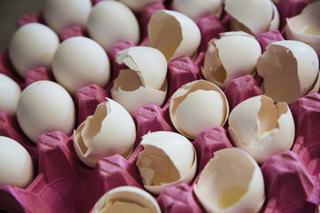Close up of white eggs and cracked white egg shells in a pink cardboard tray.
