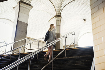 A woman walking up the steps of a subway, travelling in the city.