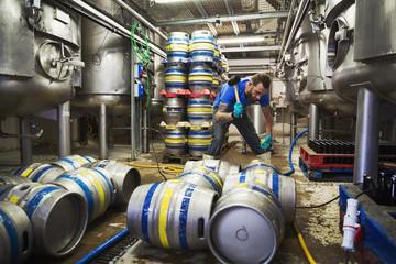 Man working in a brewery, using a mallet, closing metal beer kegs.