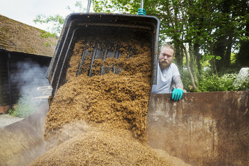 Man pouring spent grain into a large container, steam rising, during the brewing process.
