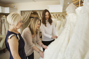 Three women, a client and two retail advisors in a wedding dress shop, looking through the choice of gowns.