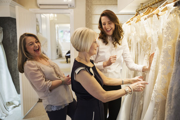 Three women in a wedding dress boutique looking at a rail of white bridal gowns, with lace and decorative fabrics. A bride to be and two sales assistants laughing.