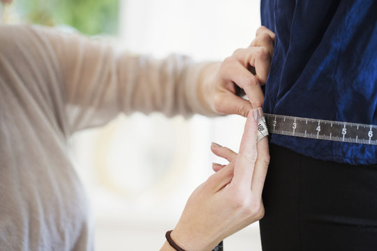 A sales assistant, dressmaker or seamstress, taking the measurements of a client in a wedding dress shop.