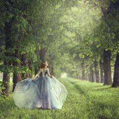 Tylny widok trwanie młoda piękna blondynki kobieta w błękit sukni