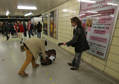 A Honduran man seeking refugee status in Canada, gives money to a subway entertainer in Toronto