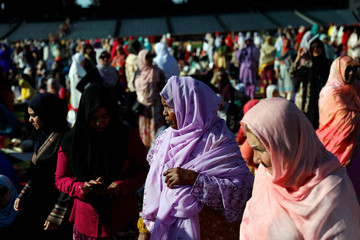 Muslim women gather on the baseball field for the celebration of the Eid al-Fitr holiday, the end of the holy month of Ramadan at Angel Stadium of Anaheim in Anaheim, California