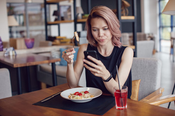 Attractive woman using smartphone and eating in a cafe.