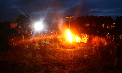 People dance at the campfire as they take part in the Ivan Kupala festival in the town of Rakov