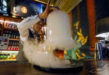 A bartender prepares a Sigara Manhattan cocktail at Barmaglot bar in Almaty