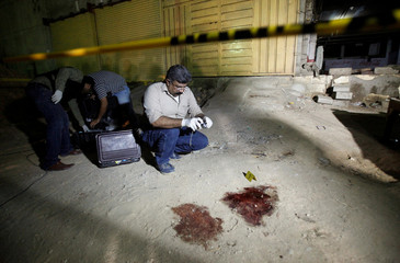 A security official takes pictures at the site of a gun attack that killed four policemen in Karachi, Pakistan