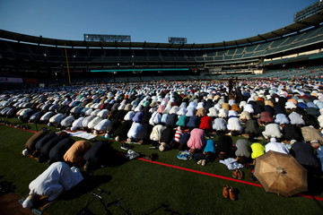 Dr. Muzammil Siddiqi of the Islamic Society of Orange County prays with Muslims gathered for the celebration of the Eid al-Fitr holiday, the end of the holy month of Ramadan at Angel Stadium of Anaheim in Anaheim, California