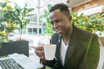 Businessman sitting in a sidewalk cafe with laptop drinking coffeew