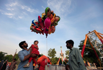 A man buys balloons for his daughter while visiting a park to celebrate the Eid al-Fitr holiday in Rawalpindi
