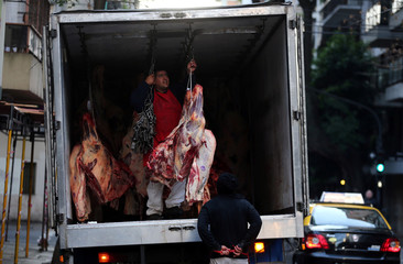 Butchers unload carcasses of beef from a truck outside a butcher shop in Buenos Aires