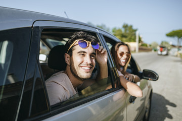 Happy young man and woman in a car looking out the window
