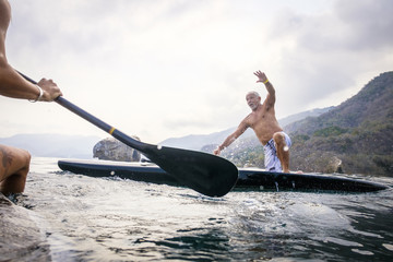 Mexico, Banderas Bay, Los Arcos National Marine Park, man falling from paddleboard