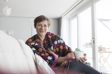 Portrait of smiling woman relaxing with cup of coffee on the couch