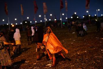 Reveller walks in the rain at Glastonbury Festival