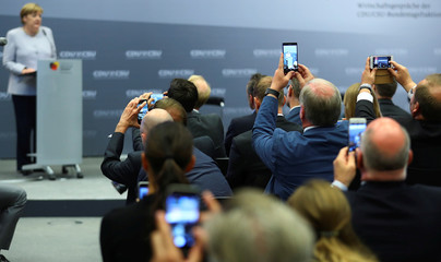 People take pictures with smartphones durind the speech of German Chancellor Merkel at a party meeting in Berlin