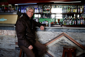 A costumer poses for a picture while drinking whisky at a bar in Montevideo