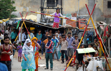 A girl performs circus tricks in a slum area of Ghaziabad