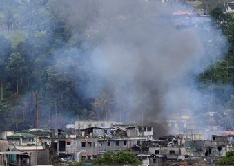 Smoke is seen as government troops continue their assault against insurgents from the Maute group, who have taken over parts of Marawi city