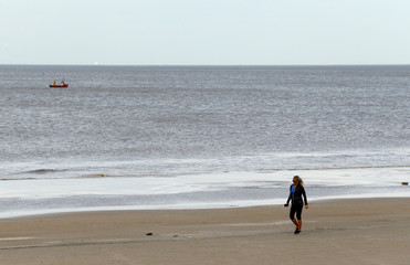 A woman jogs by Montevideo's beach of Carrasco during an unseasonal warm day