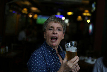 A woman gestures for a photo during a beer tasting at a bar in Rio de Janeiro