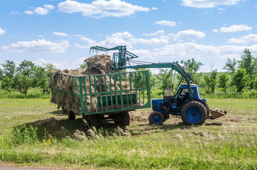Front loader loads hay in the trailer / Photo taken in Russia, in the Orenburg region