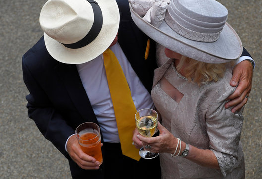 Racegoers embrace as they drink beer and wine at the Ascot racecourse at Ascot